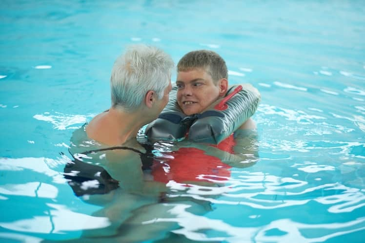 Een begeleider en cliënt aan het zwemmen
